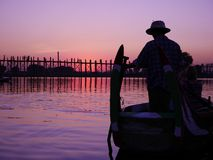 Boat rowing near U Bein bridge in the sunset Royalty Free Stock Image