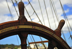 Boat Rudder-Wheel. Blue sky and a view of the rudder-wheel of an old  wooden ship Royalty Free Stock Images