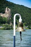 Boat`s bell on a river with a castle in the background stock photography