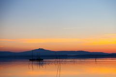 Boat's silhouette in the sunset. Lovely sunset in Lake Trasimeno, Italy Stock Photography