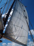 Boat Sail Pointing To Blue Skies. The sail of the Schooner reaches out for the bright blue sky. White puffy clouds passed by Stock Images