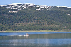 Boat Sailing Across Snow Covered Mountain Lake Stock Photo