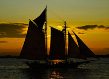 Boat sailing against crimson sunset - saturated silhouette. Sailboat sailing against deep orange crimson sunset on calm water Stock Image