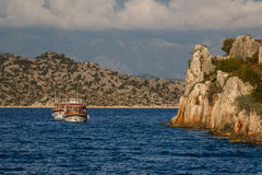 Boat sailing along ruins of the ancient town Royalty Free Stock Images
