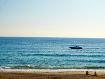 Boat is sailing along seashore some people are sitting on the sand. Boat is sailing along seashore in Turkey stock photos