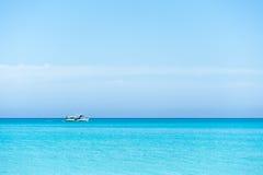 Boat sailing on blue Caribbean sea. On a sunny summer day. Empty beach Royalty Free Stock Photos