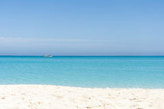 Boat sailing on blue Caribbean sea. On a sunny summer day. Empty beach Stock Images