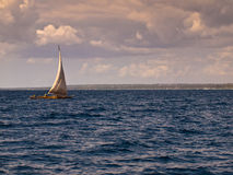 Boat sailing in the blue sea. On a background of clouds Royalty Free Stock Photography