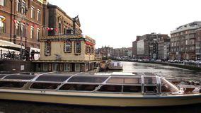 Boat sailing on a canal in Amsterdam. Amsterdam is the capital of the Netherlands and the canals and harbours fill a full quarter of the city surface stock video