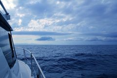 Boat sailing in cloudy stormy day blue ocean. Sea, yacht side view Royalty Free Stock Image