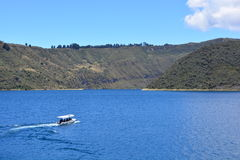 Boat sailing on the Cuicocha lake, in Otavalo, Ecuador. A boat with tourists sailing on the Cuicocha lake, a lake inside the crater of an active volcano, in stock photo
