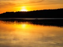 Boat sailing in the distance at sunset. Silhouette of a boat on the river royalty free stock photography