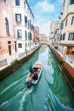 Boat sailing in italian water channel Stock Images