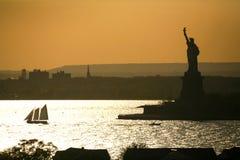 Boat sailing next to Liberty Statue Royalty Free Stock Photos