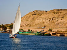 Boat sailing at Nile River. A mountain in the background and some boats in the shore Stock Image