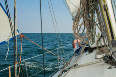 A boat sailing in the ocean, view from the deck. Blue sky an sunny day, lots of ropes and cordage on the boat Royalty Free Stock Photo