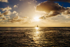 Boat sailing and plane taking off at sunset Royalty Free Stock Photo
