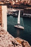 Boat sailing on a river in Marseille, France with amazing architecture in the background stock photo