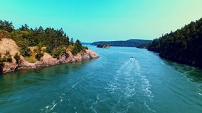 Boat sailing a river by oceanfront on a sunny day. Breathtaking aerial of a boat sailing an ocean bay between cliff rocks on a bright, windy and sunny summer day stock footage