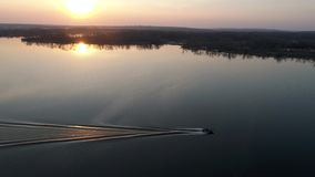 Boat sailing on the river at sunset. Video from drone. boat sailing on the river at sunset stock video footage