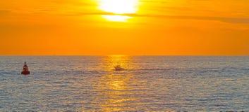 Boat sailing at sea along a coast at sunset Royalty Free Stock Photo