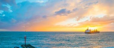 Boat sailing at sea along a coast at sunset Royalty Free Stock Images