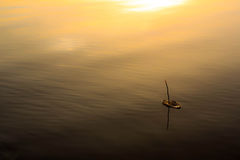 Boat sailing in sea at sunset. Aerial view of old wooden bark boat sailing in calm sea with golden sunset; Finland royalty free stock photo