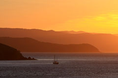Boat sailing at sunset with with hills in distance Stock Images