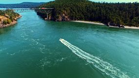 Boat sailing toward a bridge by oceanfront on a sunny day. Aerial of a boat sailing toward a bridge with moving traffic, crossing an ocean bay on a bright, windy stock video footage