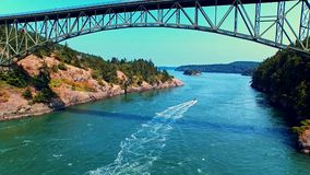 Boat sailing under a bridge by oceanfront on a sunny day. Breathtaking aerial of a boat sailing under an ocean bay bridge between cliff rocks on a bright, windy stock video
