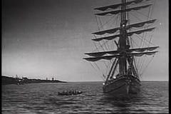 Boat sailing up to ship at sea stock video
