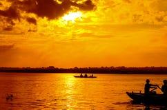boat sailors at sunrise sunset stock photo