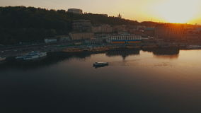 The boat sails along the river near the European river city at sunset. The boat sails along the river near the river city at sunset aerial 4K UHD stock video footage