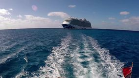 Boat sails away from cruise ship stock footage