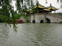Boat Sails Under Chinese Bridge. A river boat sails under a traditional Chinese bridge in a Chinese garden stock photos