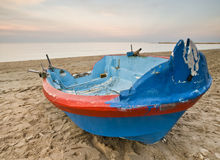 Boat on the Sand. Blue and red fishing boat on the sand of a lonely beach, with the warm light of sunset Stock Photography