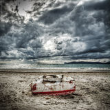 Boat on the sand under a dramatic sky Royalty Free Stock Image