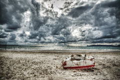 Boat on the sand under a dramatic sky Royalty Free Stock Photo
