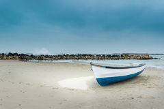 Boat on the sandy beach. Blue and white wooden boat on sandy beach Stock Photo