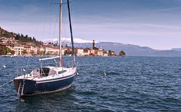 The boat and the scenery. A boat riding at anchor by the port with the city and whiten mountains on the background Stock Photo