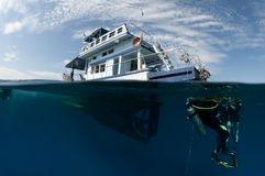 Boat and scuba divers Stock Images