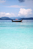 Boat in the sea. Solitary boat with an open red umbrella in the middle of the sea Royalty Free Stock Photo