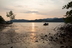 Boat at sea against the mountains at sunset at low tide stock photography
