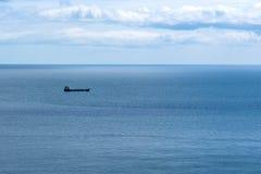 Boat at sea on the horizon. Landscape of a boat at sea navigating far into the horizon royalty free stock photos