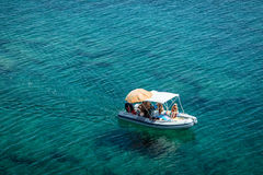 Boat in the sea. Motorboat at an open sea with some people in it in Sardinia, Italy. Beautiful turquoise water. Lots of space Stock Photography