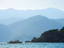 Boat in the sea near island. With mountain on background Royalty Free Stock Photography