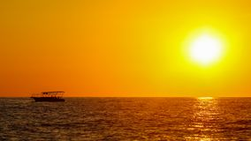 Boat on the sea in the rays of sunset.  royalty free stock photography