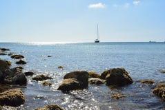 Boat on sea. Rocky coast by Meditarien Sea - Golden Bay (beach), sunny day and crystal sea Stock Photo