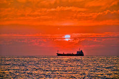 Boat on sea at sunset. Cargo ship on the horizon in the Ionian Sea at sunset Stock Image