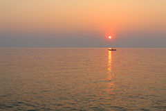 Boat in the sea at sunset. Stock Image